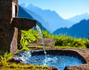 fontana in pietra fra le montagne con acqua limpida che sgorga