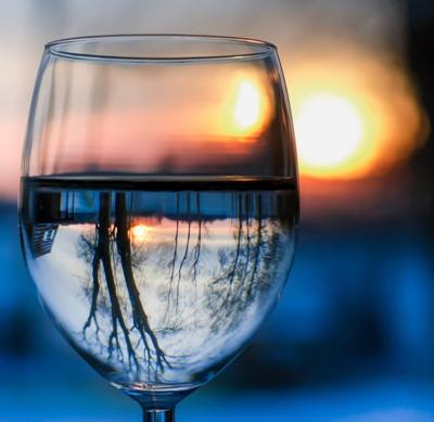 acqua depurata da pfas e agenti inquinanti dentro un bicchiere con natura riflessa nel vetro